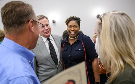 Chncellor Vitter and new graduate Deetra Wiley surrounded by smiling people.